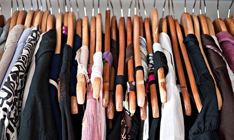 Clothes rail in cupboard, men's and women's clothing on wooden hangers